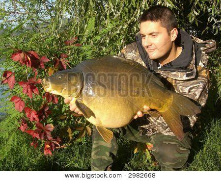 Happy fisherman with his big mirror carp poster