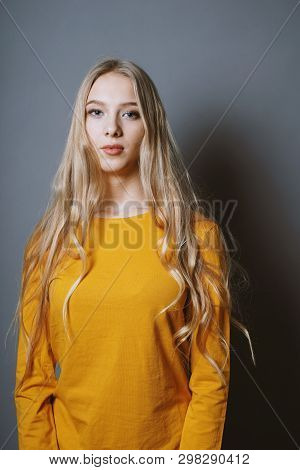 Serene Teenage Girl With Very Long Blond Hair Against Gray Background