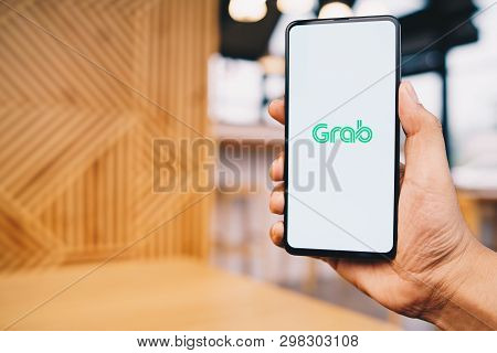Chiang Mai, Thailand - Mar. 23,2019: Man Holding Xiaomi Mi Mix 3 With Grab Apps On Screen. Grab Is S