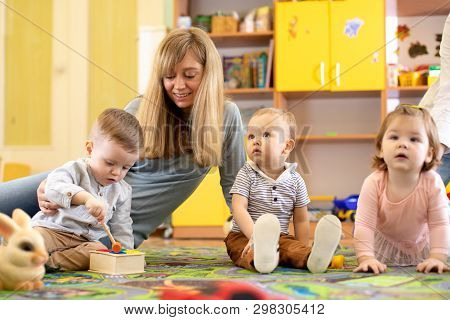 Kindergarten Teacher Looking After Children In Daycare. Little Toddlers Play Together In Nursery.