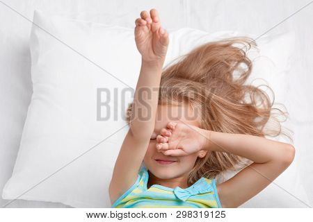 Photo Of Small Adorable Cute Child Covers Eyes, Stretches In Bed, Dressed In Pyjamass, Lies On Comfo