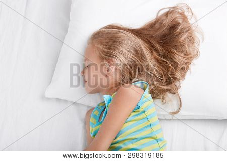 Sideways Shot Of Small Kid Wears Nightwear, Being Deep In Sleep, Rests At Bed, Lies On White Bed, En