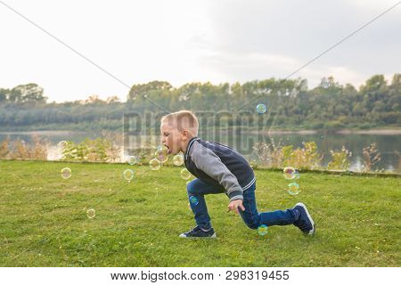 Chilhood, People Concept - Young Boy Playing With Soap Bubbles