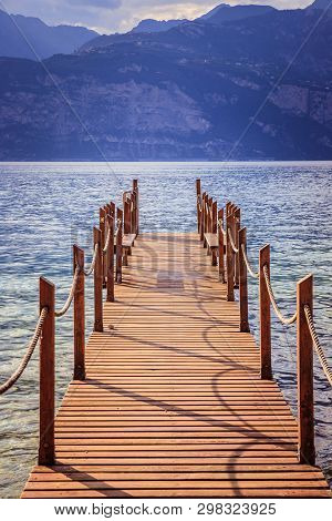 Summer Holiday: Wooden Dock Pier Over Blue Lake Water. Cloudy Evening Scenery.