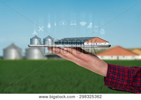 Farmer Holds A Tablet With A Modern Smart Farm. Digital Transformation In Agriculture.