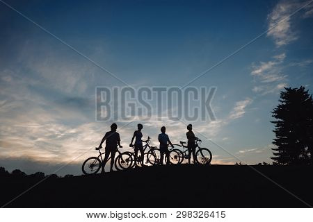 Four Cyclist On Hill At Evening Sky. Group Of Cyclists Walking With Bicycles At Sunset Sky. Happy We