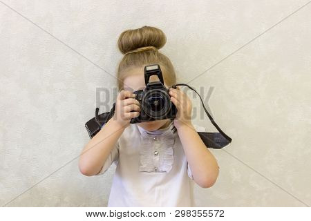 A little girl in business clothes holds a reflex camera in her hands in front of her face. The child wants to take a picture. The baby learns to take pictures and studies the complex technique poster