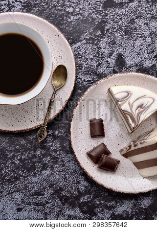Cup Of Coffee And Delicious Jelly Dessert With White & Brown Layers, Milky Glaze And Pieces Of Dark