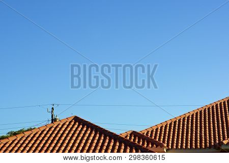 View of three orange terra cotta clay roof tops against a clear blue sky in bonita springs florida with deep shadows from morning light. and power lines in the background. poster