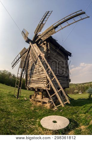 Wooden Windmill And Millstone On The Hillside Against The Backdrop Of The Rural Landscape. Selective