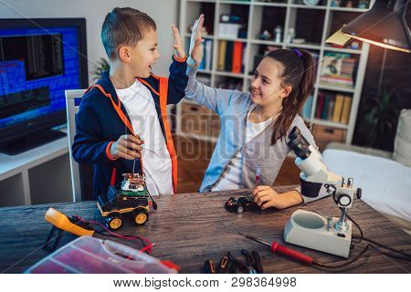 Happy Smiling Boy And Girl Constructs Technical Toy And Make Robot. Technical Toy On Table Full Of D