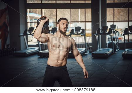 Athletic Young Man With Beard Doing Lifting Weight At The Gym Opposite The Camera. Exercise On The S