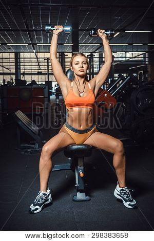 Perfect Sexy Girl In Orange Top, Short Yellow Pants Doing An Exercise On The Shoulders With A Dumbbe