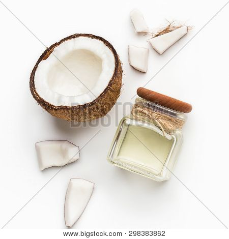 Fresh Coconut And Jar Of Coconut Oil On White Background, Top View. Coconut Treatment Concept