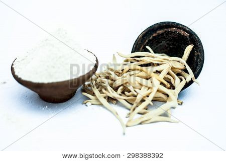 Popular Indian & Asian ayurvedic herb isolated on white in a clay bowl i.e. Musli or safed musli or Chlorophytum borivilianum with its powder in a clay bowl used in many ayurvedic medicines. poster