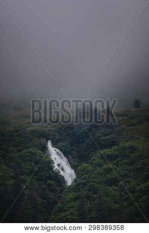 Waterfall In The Misty Green Forest On A Cloudy Day In Alaska