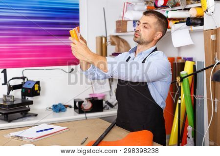 Man Designer And Print Operator With Paper Print At Print Manufacturing