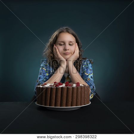 Dark-haired Girl On A Diet Looks At A Chocolate Cake, Struggling With The Desire To Eat It