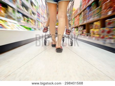 Walking Through Supermarket Aisle With A Boy On The Shopping Cart