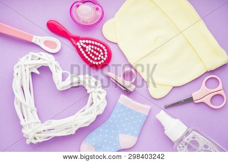 Newborn baby story. Strow heart and childrens toys, scissors, baby bottle, nipple, hairbrush on violet background poster