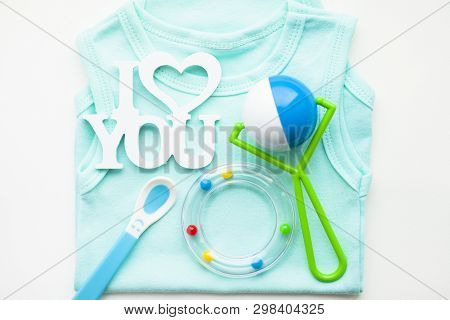Newborn baby story. T-shirt and childrens toys, scissors, baby bottle, nipple, hairbrush on white background poster
