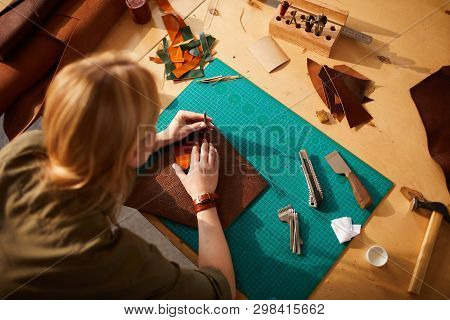 Above view portrait of female artisan making leather bag in leatherworking atelier lit by sunlight, copy space poster