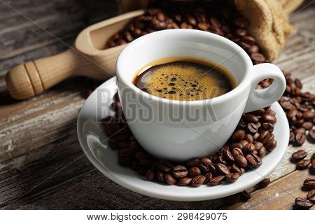 Coffee Cup And Roasted Coffee Beans In A Burlap Sack On A Wooden Rustic Table Close Up View On Rusty