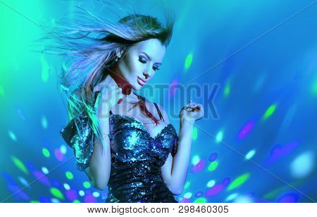 Fashion model sexy woman dancing on disco party in neon light, night club dancer, beautiful model girl, Art design. Disco dancer posing in UV, colorful lights. Holiday Make up. Colorful background