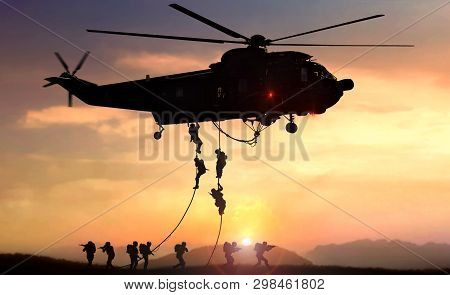 Military Commando Helicopter Drops In Silhouette During Sunset