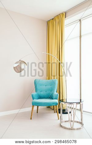Conceptual Light  Interior Of Living Room With Blue Armchair, Metallic Standing Lamp,  Glass Round C