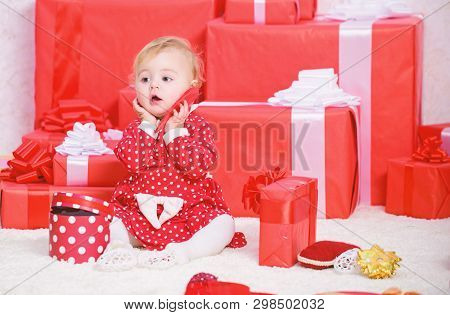 Sharing Joy Of Baby First Christmas With Family. Little Baby Girl Play Near Pile Of Gift Boxes. Gift