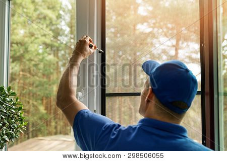Man Installing Mosquito Net Wire Screen On House Window
