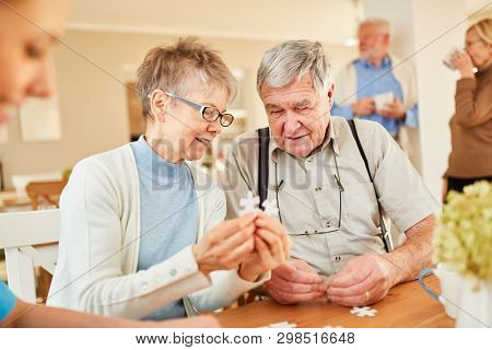 Senior couple with dementia playing puzzle in retirement home or nursing home