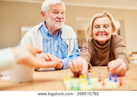 Happy senior pensioner couple is having fun at board game in retirement home or at home