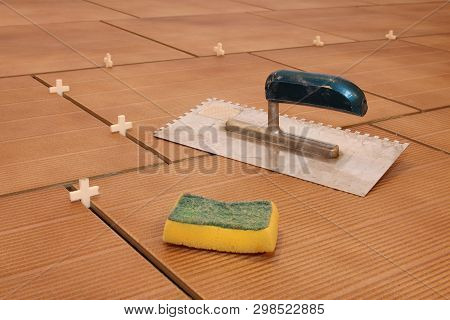Laying Ceramic Tiles, Tile Spacer And Ohter Tiling Tool. Tiler Placing Floor Tile In Position Using