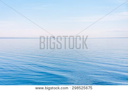 Light And Simple Landscape With Blue Sky, Light Clouds And Wavy Blue Water With A Ship In A Distance