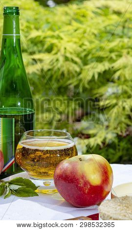 Glass With Fresh Cold French Apple Cider Drink Served With Apples In Green Garden