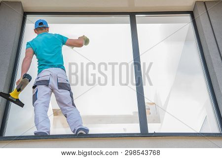Caucasian Men Cleaning Large Residential Window Outside Of The House. Cleaning Service Business.
