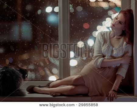 romantic beautiful woman and a cat sitting on a window at winter night