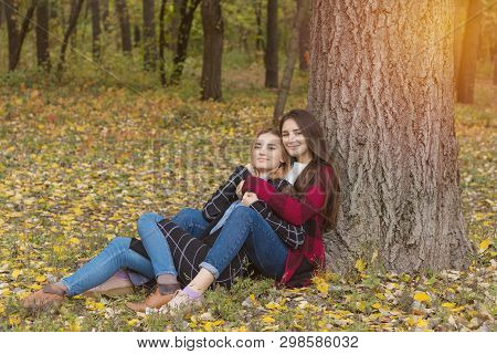 Two Cute Beautiful Young Women Relaxing In The Autumn City Park. Emotion And Activity.