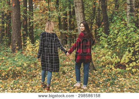 Two Cute Beautiful Young Women Walking Footpath In The Autumn City Park. Emotion And Activity.