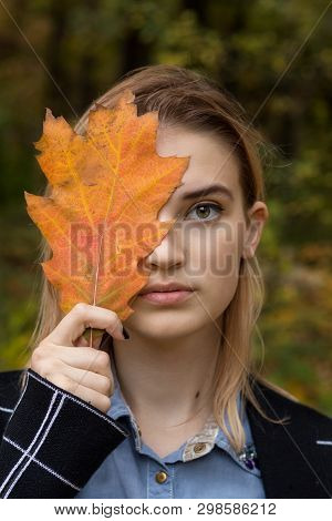 Creative Portrait Young Woman In The Autumn City Park. Girl Face Close Up, Half Face Behind A Yellow