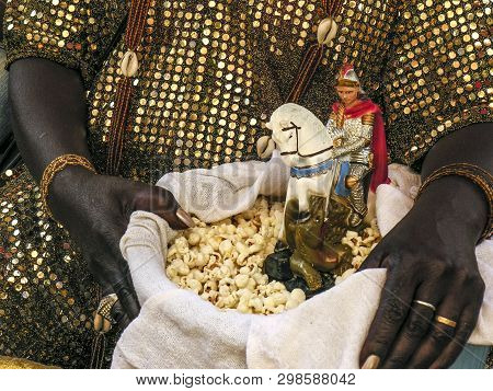 Mother Of Candomble Saint Holds A Basket With Popcorn And The Image Of Saint George (ogum) In Front
