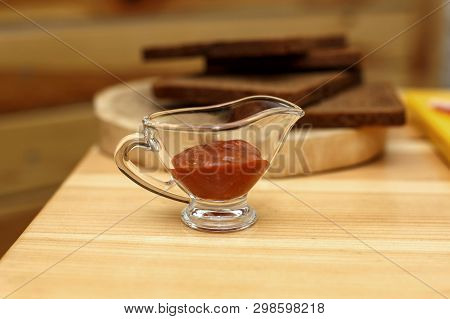 Glass Sauceboat With Ketchup On Wooden Table.