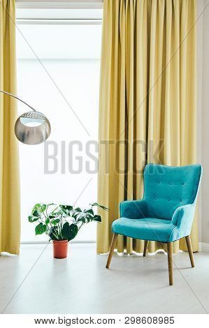 Conceptual Light  Interior Of Living Room With Blue Armchair, Metallic Round Shape Standing Lamp, Mo