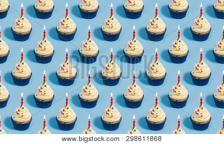Seamless pattern with birthday cupcakes and candles on a blue background