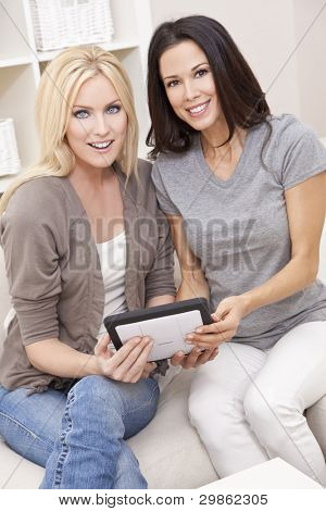 Overhead photograph of two beautiful young women at home sitting on sofa or settee using a tablet PC computer and smiling