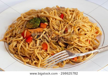 A meal of vegetable noodles with a fork