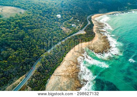 Aerial View Of Vehicles Driving On Great Ocean Road Along Scenic Coastline Near Lorne, Australia
