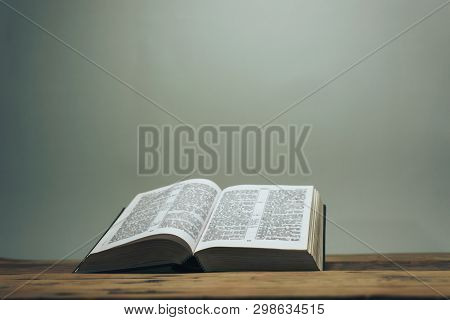 Open Holy Bible On A Old Oak Wooden Table.  Grey Wall Background.
